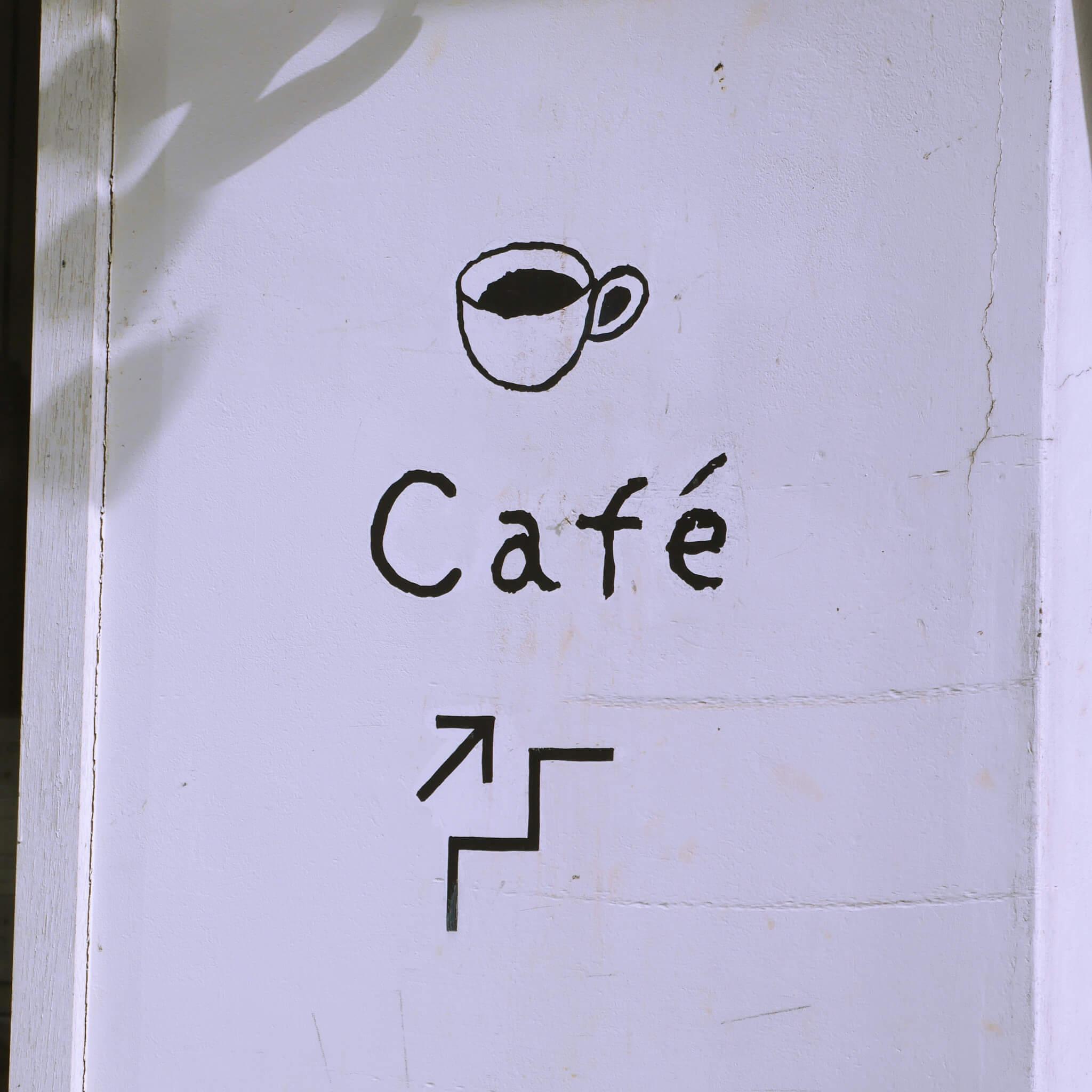 白い壁のカフェの案内