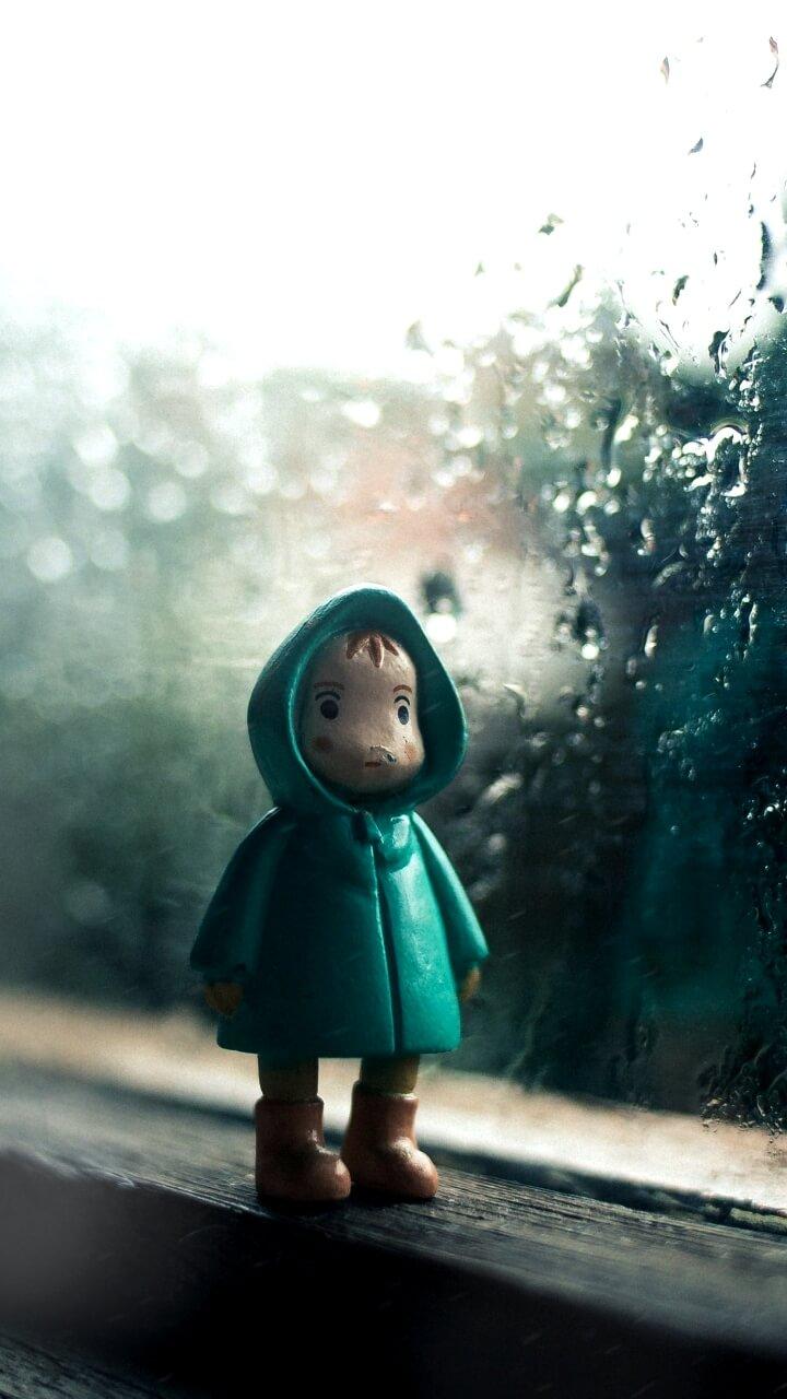 雨の日の窓とレインコート姿の人形